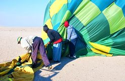 Na omhoog het landen van een team van helperspakken een hete luchtballon