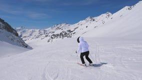 Na opinião da parte traseira do movimento, esquiador da mulher que esquia abaixo da inclinação da montanha em esquis filme