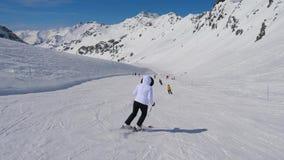 Na opinião da parte traseira do movimento, esquiador da mulher que esquia para baixo do resort de montanha filme