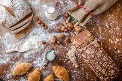 Na padaria, ainda na vida com mini croissant, no pão, no leite, nas porcas e na farinha Fotografia de Stock Royalty Free