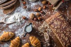 Na padaria, ainda na vida com mini croissant, no pão, no leite, nas porcas e na farinha Foto de Stock