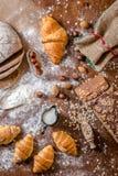 Na padaria, ainda na vida com mini croissant, no pão, no leite, nas porcas e na farinha Fotografia de Stock