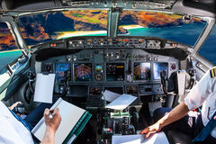 Na Pali Coast cockpit. Airplane cockpit flying on Na Pali coast, Kauai, Hawaii, United States, with pilots arms and blank white papers for copy space Royalty Free Stock Images