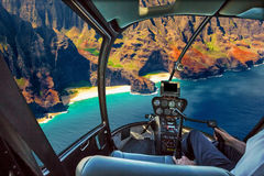 Na Pali Coast scenic flight. Helicopter cockpit flies in Na Pali coast, Kauai, Hawaii, United States, with pilot arm and control board inside the cabin Stock Images