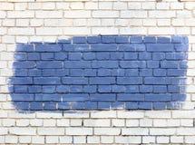 Na parede de tijolo velha branca o fragmento selecionado é pintado com pintura azul Foto de Stock