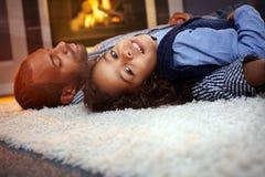 Na podłoga małej dziewczynki i ojca lying on the beach w domu Zdjęcia Royalty Free