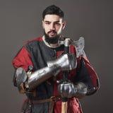 Na popielatym tle średniowieczny rycerz Portret brutalny brudny twarz wojownik z łańcuszkowej poczta zbroi czerni i czerwieni ubr Zdjęcia Stock