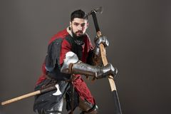 Na popielatym tle średniowieczny rycerz Portret brutalny brudny twarz wojownik z łańcuszkowej poczta zbroi czerni i czerwieni ubr Fotografia Royalty Free