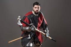 Na popielatym tle średniowieczny rycerz Portret brutalny brudny twarz wojownik z łańcuszkowej poczta zbroi czerni i czerwieni ubr Obrazy Stock