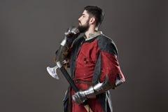 Na popielatym tle średniowieczny rycerz Portret brutalny brudny twarz wojownik z łańcuszkowej poczta zbroi czerni i czerwieni ubr Zdjęcia Royalty Free