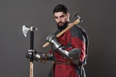 Na popielatym tle średniowieczny rycerz Portret brutalny brudny twarz wojownik z łańcuszkowej poczta zbroi czerni i czerwieni ubr Zdjęcie Stock