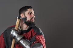 Na popielatym tle średniowieczny rycerz Portret brutalny brudny twarz wojownik z łańcuszkowej poczta zbroi czerni i czerwieni ubr Obraz Stock