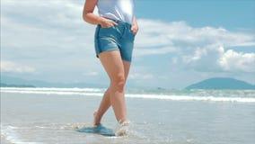 Na praia tropical um close-up da morena bonito europeia dos pés das mulheres vai sob o verão quente Sun ao longo do tropical filme