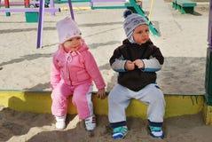 Um menino e uma menina que sentam-se em uma caixa de areia Imagens de Stock