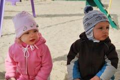 Um menino e uma menina que sentam-se em uma caixa de areia Fotografia de Stock