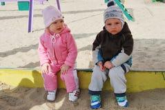 Um menino e uma menina que sentam-se em uma caixa de areia Fotos de Stock Royalty Free
