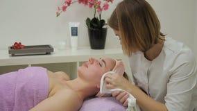 Na procedure veegt de schoonheidsspecialist gezicht van vrouwelijke patiënt met handdoek af stock video