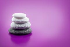 Na purpurowym tle asortowani zrównoważeni kamienie Fotografia Royalty Free