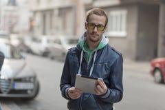 Na rua: Computador da tabuleta de Ipad do uso do homem Foto de Stock Royalty Free