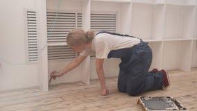Na sala o louro está ajoelhando-se e cobre a escova de assoalho com a primeira demão vídeos de arquivo