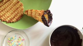 Na stołów kłamstwach gofra rożek zamaczający w rozciekłej czekoladzie i dekorujący z barwi kropi zdjęcie wideo