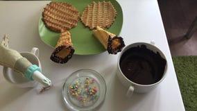 Na stołów kłamstwach gofra rożek zamaczający w rozciekłej czekoladzie i dekorujący z barwi kropi Tam są składniki dla c zbiory wideo