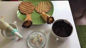 Na stołów kłamstwach gofra rożek zamaczający w rozciekłej czekoladzie i dekorujący z barwi kropi Tam są składniki dla c zbiory