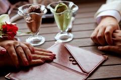 Na stołowym kłamstwie ręki państwo młodzi obok pierścionku na menu falcówce i Fotografia Royalty Free