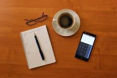 Na stole filiżanka natychmiastowej kawy notatnik i szkła dzwoni zdjęcia stock