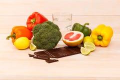 Na stole jest czekolada, szkło wodni i pożytecznie cytrusów owoc i warzywo dieta zdrowa Boczny widok _ Obrazy Royalty Free