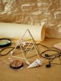 Na stole jest kompas, powiększać - szkło, metalu ostrosłup z geometrycznymi kształtami, hełmofony, złoty lekki tło obraz royalty free