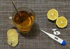 Na stole szkło herbata z cytryną Termometr, pigułki i cytryna kliny, obraz royalty free