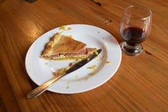 Na stole tam jest niedokończony czerwone wino w szkle i kawałku tort obrazy royalty free