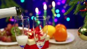 Na stole z prezentami mężczyzna otwiera shompank i nalewa je w szkła na nowego roku ` s tle zbiory wideo