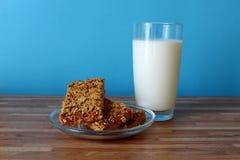 Na tabela é um vidro do leite com cookies Fotos de Stock