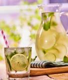 Na tabela de madeira é o jarro de vidro com bebida transparente Foto de Stock