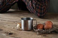 Na tabela de madeira é uma caneca de água, uma fatia de pão, potatoe Foto de Stock
