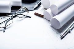Na tabela de madeira há desenhos, compassos, lápis, régua e vidros fotos de stock