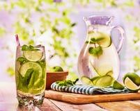 Na tabela de madeira é o jarro de vidro com bebida transparente Fotos de Stock