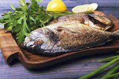 Na tabela de madeira uma placa com dois roasted o dorado dos peixes da carpa Fotos de Stock