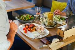 Na tabela, dois homens comem o jantar, comem um bife, com uma salada em uma placa branca, com uma forquilha e uma faca em suas mã Fotos de Stock