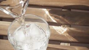 Na tabela em um vidro do gelo derrame o movimento lento da água vídeos de arquivo