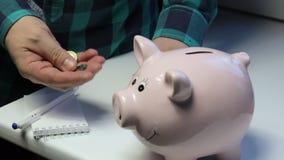 Na tabela há um mealheiro sob a forma de um porco cor-de-rosa O homem da tabela da moeda, joga-os no mealheiro makes video estoque