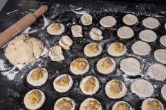 Na tabela preta apresentou os círculos da massa crua enchidos com carne e batatas da galinha para cozer foto de stock royalty free
