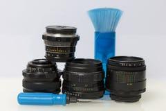 Na tabela são as lentes velhas, uma chave de fenda e uma escova para escovar fora a poeira imagens de stock royalty free