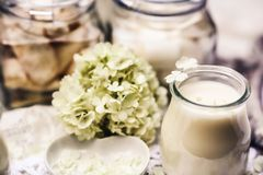 Na tabela são as velas brancas e as flores macias Imagens de Stock Royalty Free