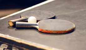 Na tabela são duas raquetes de tênis de mesa velhas e uma bola fotografia de stock