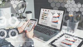 Na tabela são o portátil, a tabuleta digital com cartas, os gráficos e os diagramas em telas Fotografia de Stock Royalty Free