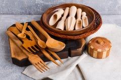 Na tabela são uma placa e uma cesta em que está um grupo de dispositivos diferentes da cozinha feitos da madeira Fotografia de Stock