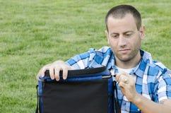 Na trawie mężczyzna obsiadanie Zdjęcia Royalty Free